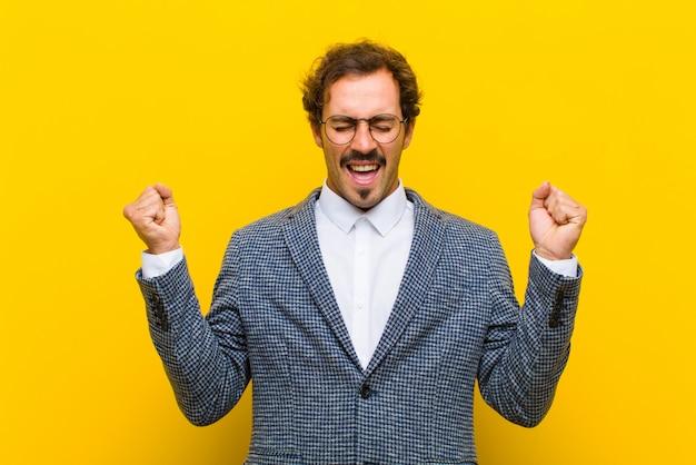 Młody przystojny mężczyzna patrząc bardzo szczęśliwy i zaskoczony, świętuje sukces, krzyczy i skacze pomarańczową ścianę