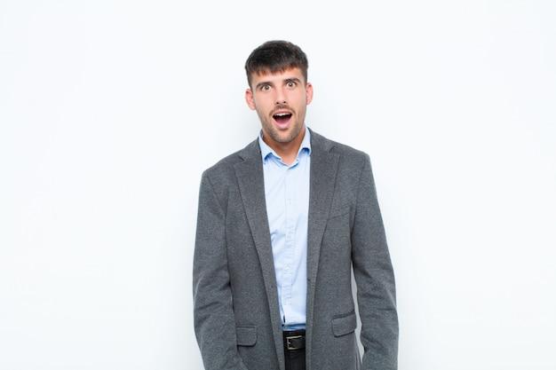Młody przystojny mężczyzna, patrząc bardzo zszokowany lub zaskoczony, wpatrując się z otwartymi ustami mówiąc wow nad białą ścianą