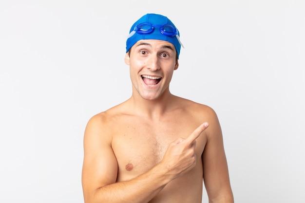 Młody przystojny mężczyzna patrząc podekscytowany i zaskoczony, wskazując na bok. koncepcja pływaka