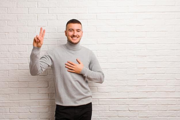 Młody przystojny mężczyzna patrząc szczęśliwy, pewny siebie i godny zaufania, uśmiechając się i pokazując znak zwycięstwa, z pozytywnym nastawieniem do płaskiej ściany