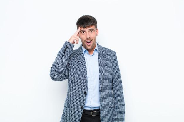 Młody przystojny mężczyzna, patrząc zaskoczony, z otwartymi ustami, zszokowany, realizując nową myśl, pomysł lub koncepcję na białej ścianie