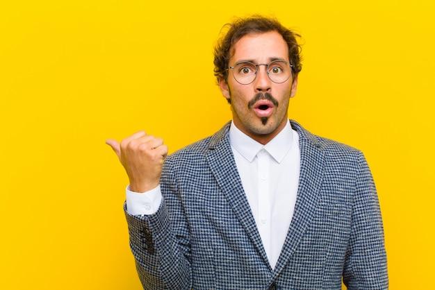 Młody przystojny mężczyzna patrząc zdziwiony z niedowierzaniem, wskazując na obiekt z boku i mówiąc wow, niewiarygodne na pomarańczowej ścianie