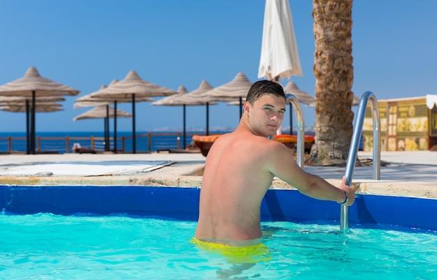 Młody przystojny mężczyzna patrzący w kamerę, gdy wychodzi na basen w hotelu w słoneczny letni dzień