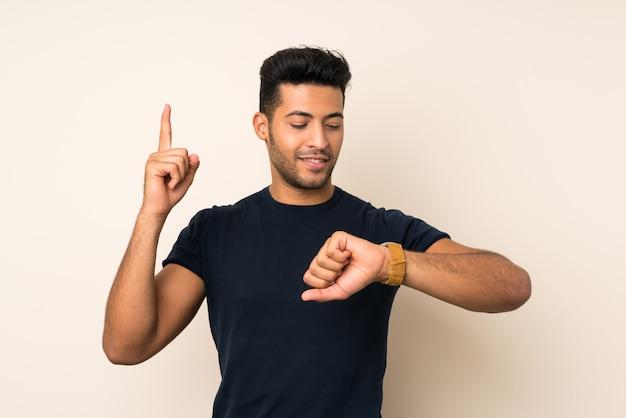 Młody przystojny mężczyzna patrzeje ręka zegarek