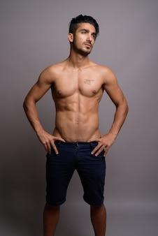 Młody przystojny mężczyzna perski bez koszuli na szarym tle