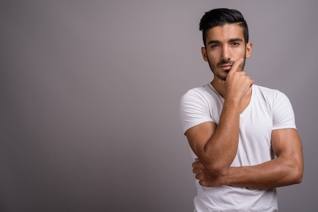 Młody przystojny mężczyzna perski na szarym tle