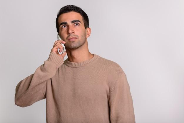 Młody przystojny mężczyzna perski rozmawia przez telefon podczas myślenia