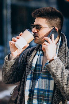 Młody przystojny mężczyzna pije kawę na zewnątrz i używa telefon