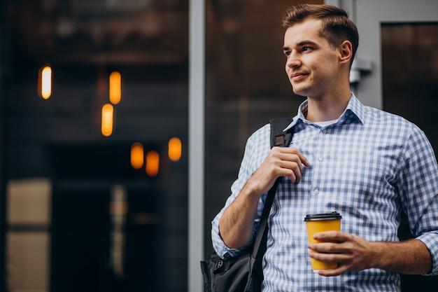 Młody przystojny mężczyzna pije kawę na zewnątrz