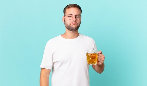 Młody przystojny mężczyzna pije kufel piwa