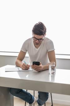 Młody przystojny mężczyzna pisze coś na papierowym notatniku i trzyma mobilnego mądrze telefon w domu. pomysł na biznes.