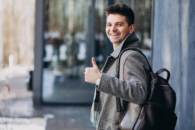 Młody przystojny mężczyzna podróżnik używa telefon outside
