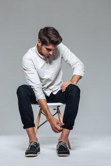 Młody przystojny mężczyzna podwija spodnie siedząc na krześle odizolowanym na szarej ścianie