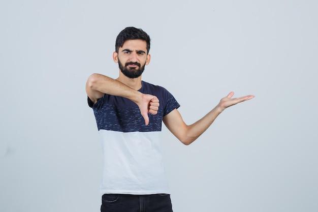 Młody przystojny mężczyzna pokazując kciuk w dół