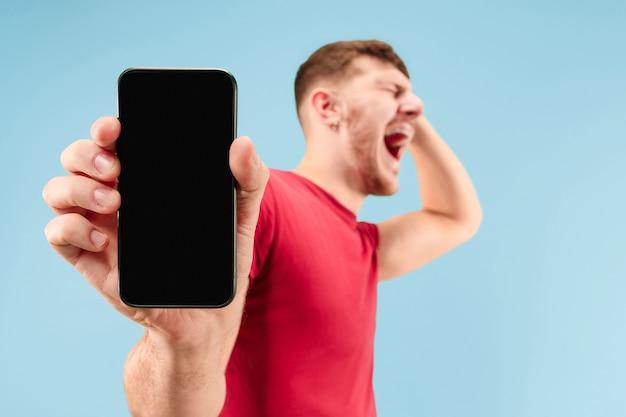 Młody przystojny mężczyzna pokazuje ekran smartfona na niebieskim tle z niespodzianką. ludzkie emocje, koncepcja wyraz twarzy. modne kolory