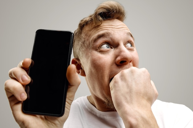 Młody przystojny mężczyzna pokazuje ekran smartfona na szarym tle z twarzą niespodzianki. ludzkie emocje, koncepcja wyrazu twarzy