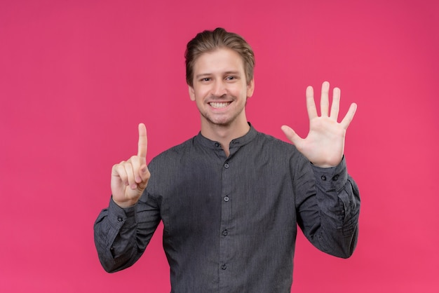 Młody przystojny mężczyzna pokazuje palcami numer sześć i wskazuje w górę