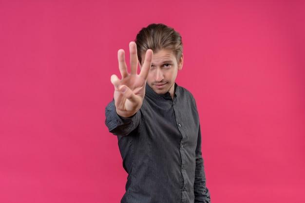 Młody przystojny mężczyzna pokazuje palcami numer trzy i wskazuje w górę