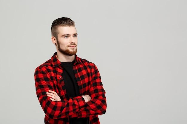Młody przystojny mężczyzna pozuje nad szarości ścianą.