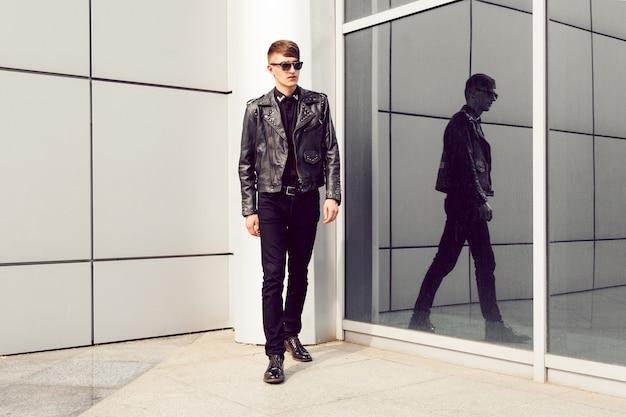 Młody przystojny mężczyzna pozuje w pobliżu nowoczesnego centrum biznesowego, ubrany w stylową skórzaną kurtkę z kolcami, czarne dżinsy i okulary przeciwsłoneczne, brutalny wygląd.