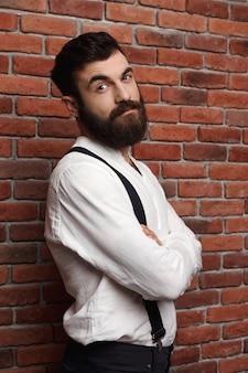 Młody przystojny mężczyzna pozuje z krzyżować rękami na ściana z cegieł.