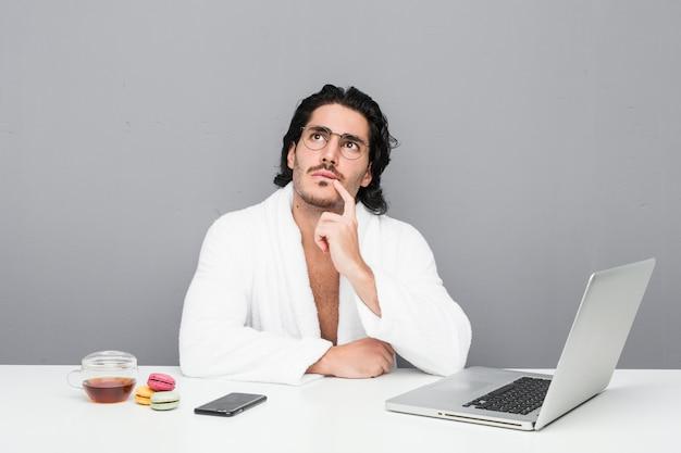 Młody przystojny mężczyzna pracujący po prysznic patrząc z ukosa z wyrazem wątpliwości i sceptycyzmu.