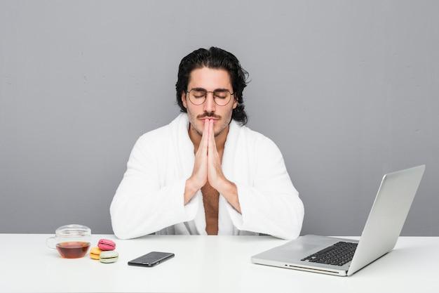 Młody przystojny mężczyzna pracujący po prysznicu, trzymając się za ręce w modlitwie w pobliżu ust, czuje się pewnie.