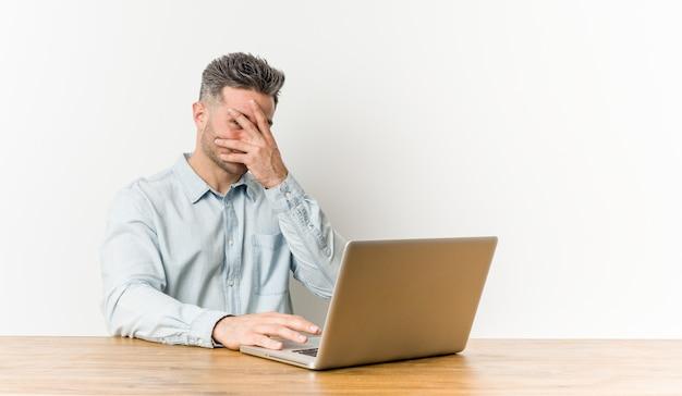 Młody przystojny mężczyzna pracujący z laptopem mruga palcami, zakłopotany zakrywając twarz.