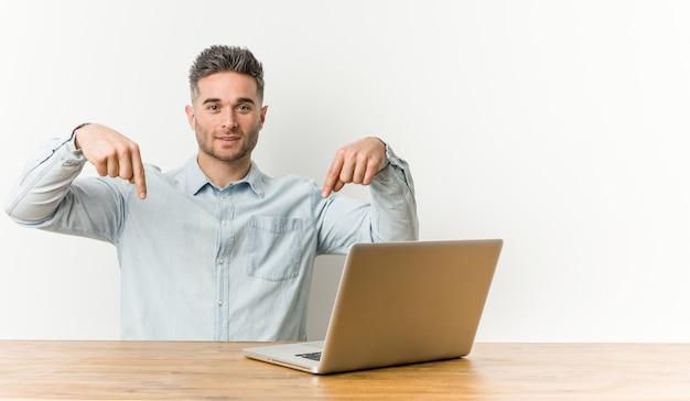 Młody przystojny mężczyzna pracujący z laptopem wskazuje palcami w dół, pozytywne uczucie.