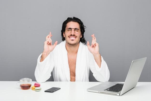 Młody przystojny mężczyzna pracuje po prysznic krzyżuje palce dla mieć szczęście