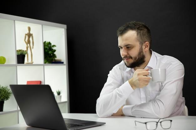 Młody przystojny mężczyzna pracuje przy komputerze w domowym biurze, koncepcja e-learningu