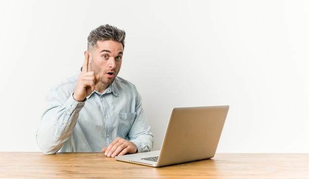 Młody przystojny mężczyzna pracuje z jego laptopem ma pomysł, inspiraci pojęcie.