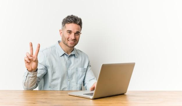 Młody przystojny mężczyzna pracuje ze swoim laptopem pokazuje numer dwa palcami.