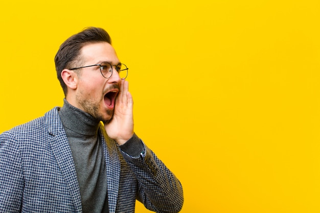 Młody przystojny mężczyzna profil widok, patrząc szczęśliwy i podekscytowany, krzycząc i dzwoniąc do copyspace na ścianie pomarańczowy strony