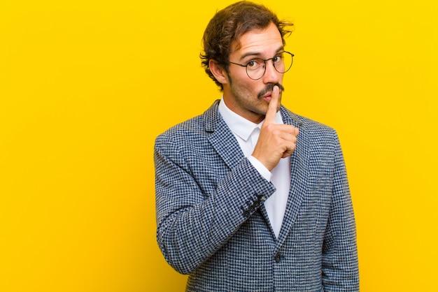 Młody przystojny mężczyzna prosi o ciszę i ciszę, gestykuluje palcem przed ustami, mówiąc: ćśśśś lub trzymaj sekret przed pomarańczą