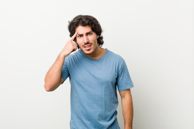 Młody przystojny mężczyzna przeciw białej ścianie pokazuje rozczarowanie gest z palcem wskazującym.