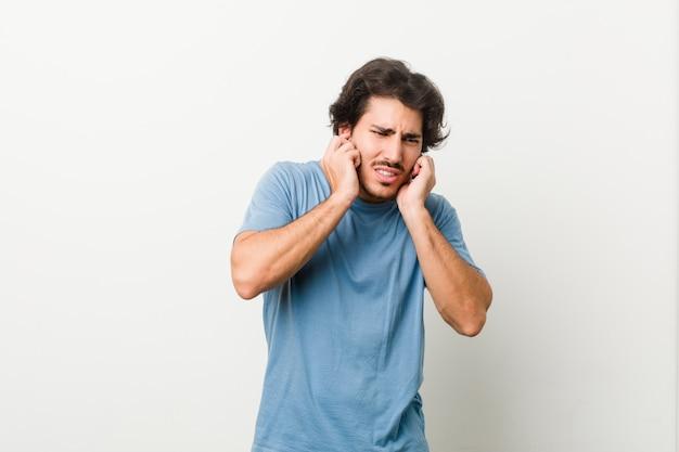 Młody przystojny mężczyzna przeciw białej ścianie zakrywa ucho z rękami.