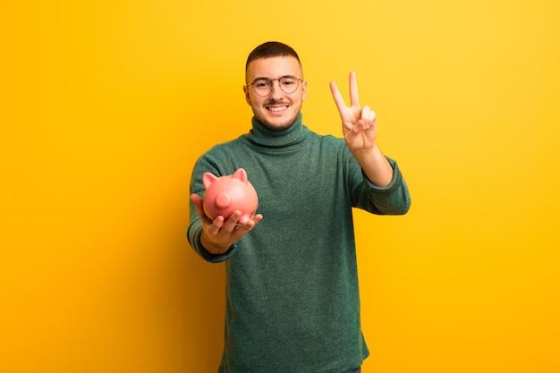 Młody przystojny mężczyzna przeciw płaskiej ścianie z prosiątko bankiem