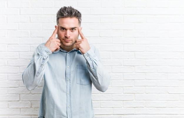Młody przystojny mężczyzna przy ścianie z cegły skupił się na zadaniu, trzymając palce wskazujące głową.