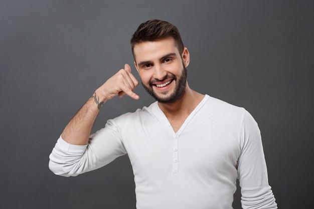 Młody przystojny mężczyzna pyta, aby zadzwonić do niego na szarej ścianie