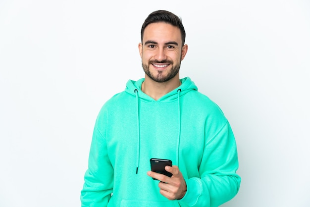 Młody przystojny mężczyzna rasy kaukaskiej na białym tle przy użyciu telefonu komórkowego