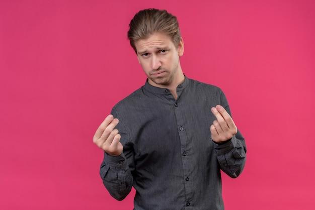 Młody przystojny mężczyzna robi pieniądze gest z rękami z sceptycznym wyrazem twarzy