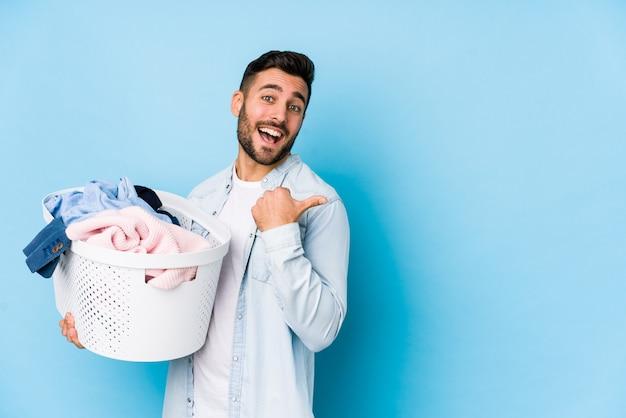 Młody przystojny mężczyzna robi pralni na białym tle punktów z kciukiem palcem, śmiejąc się i beztroski.