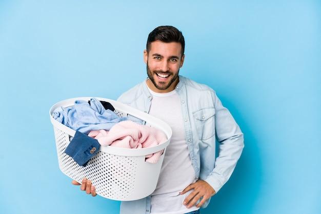 Młody przystojny mężczyzna robi pranie na białym tle śmiejąc się i zabawy.
