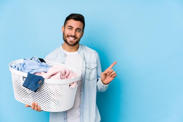 Młody przystojny mężczyzna robi pranie na białym tle, uśmiechając się i wskazując na bok, pokazując coś w pustej przestrzeni.