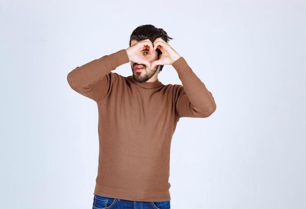 Młody przystojny mężczyzna robi serce symbol kształt rękami.