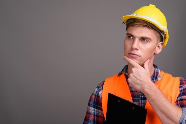 Młody przystojny mężczyzna robotnik budowlany na szarym walld