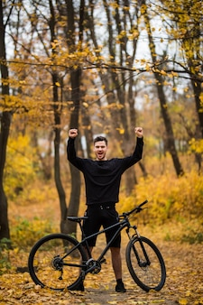 Młody przystojny mężczyzna rowerzysta po treningu z podniesionymi rękami w jesień lasu śladzie
