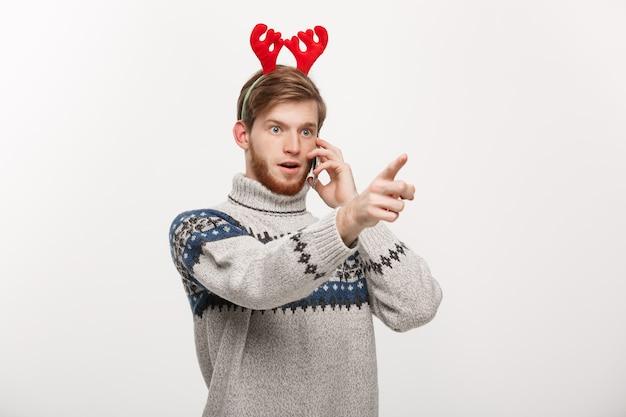 Młody przystojny mężczyzna rozmawia przez telefon i wskazując palcem z przodu.