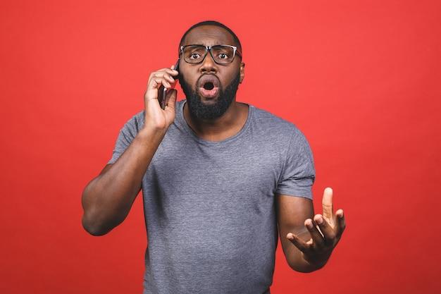 Młody przystojny mężczyzna rozmawia przez usta pokrywa telefon ręką zszokowany wstydem za błąd